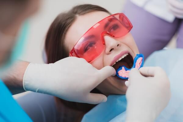 A dental patient wears protective glasses and opens her mouth for a fluoride treatment.