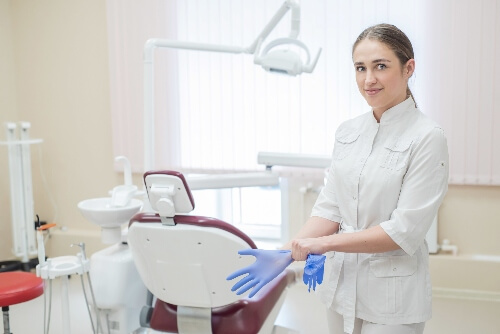 A dental Hygienist puts on personal protection equipment (PPE) gloves as a standard practice for emergency dental work.