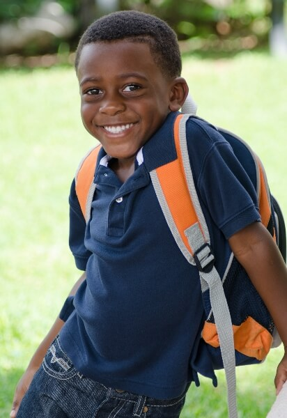 A young school kid with a backpack smiles at the camera.